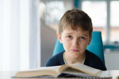 8 anni stanchi del ragazzo che fa il suo compito alla tavola Fotografia Stock