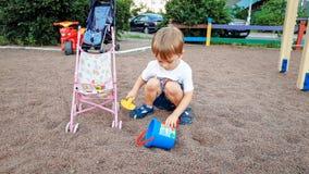 3 anni svegli del ragazzino che gioca sul campo da giuoco dei bambini in parco Sabbia di scavatura del bambino con le pale immagine stock libera da diritti