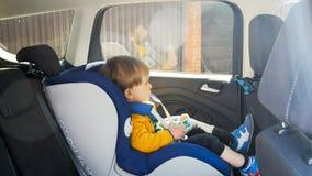 2 anni svegli del ragazzo del bambino che si siede con l'automobile del giocattolo nel sedile di sicurezza Fotografia Stock Libera da Diritti