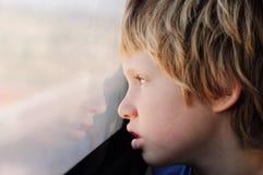 7 anni svegli del ragazzo che guarda attraverso la finestra Immagini Stock Libere da Diritti