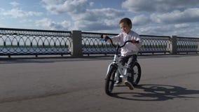 3 - 4 anni svegli di bambino del ragazzo che impara guidare la prima bici corrente dell'equilibrio video d archivio