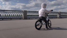 3 - 4 anni svegli di bambino del ragazzo che impara guidare la prima bici corrente dell'equilibrio archivi video