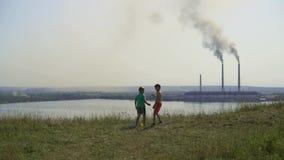 2017 anni Ucraina Gioco di bambini sui precedenti di una centrale elettrica termica Diffusioni soleggiate del fumo del nero di gi stock footage