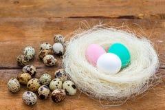 Annidi con le uova di Pasqua colorate e poche uova di quaglia ai vecchi precedenti di legno non dipinti marroni Fotografia Stock Libera da Diritti