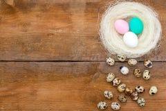 Annidi con le uova di Pasqua colorate e poche uova di quaglia ai vecchi precedenti di legno non dipinti marroni Fotografie Stock