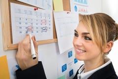 Anniversaire d'inscription de femme d'affaires sur le calendrier Photo libre de droits