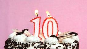 Anniversaire de célébration 10 ans avec le gâteau et bougies sur le fond rose clips vidéos