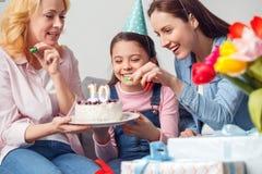 Anniversaire de mère et de fille de grand-mère ensemble à la maison se reposant jugeant le gâteau gai image stock