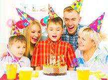 Anniversaire Le petit garçon souffle des bougies sur le gâteau d'anniversaire image libre de droits