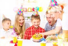 Anniversaire Le petit garçon souffle des bougies sur le gâteau d'anniversaire photos libres de droits