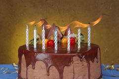 Anniversary cake. Seven lit candles on a chocolate cake Royalty Free Stock Image