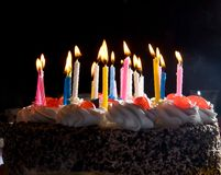 Anniversary cake. With colorful burning candles in dark Royalty Free Stock Photography