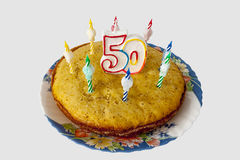 Anniversary cake with candles and numeral fifty Stock Photos