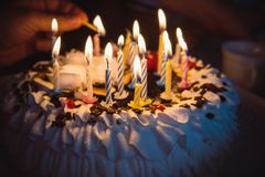Anniversary cake with hand burning candles in dark. A hand with a match lights the candles on the birthday cake with white cream. 16 sixteen candles on the Stock Image