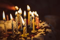 Anniversary cake with hand burning candles in dark. A hand with a match lights the candles on the birthday cake with white cream. 14 fourteen candles on the Royalty Free Stock Image