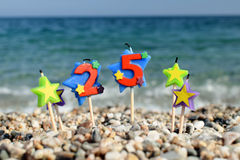 Anniversary. Candles for the 25th anniversary at the beach Royalty Free Stock Images