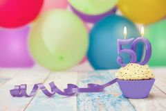 50 anniversary celebration muffin with candle. Party hats and balloons Stock Photo