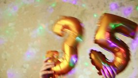 Anniversary concept, golden number 35 air balloons. Anniversary concept, hands with golden number thirty five air balloons stock footage