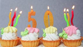 Birthday anniversary 50 years with cake and yellow numbers candles. Anniversary concept. Happy 50 birthday cakes and yellow number candles on gray background stock footage