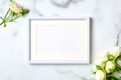 Anniversary congratulation flower background. White rose and frame with blank paper card on marble background, flat lay. Composition, top view, overhead stock photography