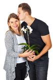 Anniversary gift. Young men kissing his girlfriend, holding an orchid - anniversary gift, on isolated Stock Images