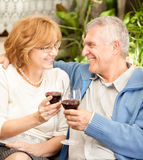 Anniversary. Happy senior couple toasting their anniversary with red wine at home ambient Stock Photography