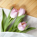 Anniversary pink tulip bouquet wrapped in white paper. Top view at bunch of fresh tulips, image concept for wedding blog, mothers Royalty Free Stock Photo