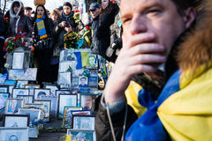 Anniversary of the Revolution of Dignity in Ukraine. KIEV, UKRAINE - NOV 21, 2014: People laying flowers near the memorial cross at the site of murder of the Royalty Free Stock Image