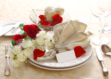 Anniversary Or Valentine Table Setting. Pretty floral anniversary or Valentine table setting of red and white roses with a fanned napkin and blank card Royalty Free Stock Image