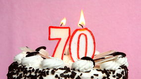 Anniversary 70 years with cake and candles on pink background. Candles as numbers 70 on cake on pink background. Can be used as Anniversary, birthday concept stock video