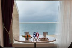 Anniversary 50 years. Happy Birthday concept. Two candles on the stylish table with food and drinks on the beautiful background of sea from the balcony Stock Photos