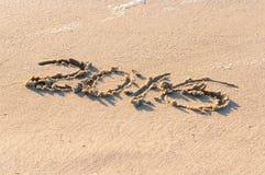 Anno 2016 scritto nella sabbia su una spiaggia contro il tramonto Immagini Stock Libere da Diritti