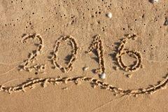 Anno 2016 scritto sulla sabbia della spiaggia Fotografia Stock