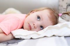 1 anno svegli di neonata che si trova a letto Fotografia Stock