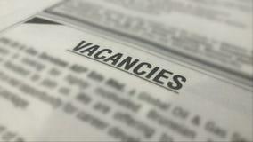 Annonces de vacances d'emploi sur un journal avec l'entourage brouillé photographie stock libre de droits