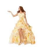Annonserar den långa klänningen för kvinnablomman, flicka den tomma handen, modeskönhetstående i den blom- kappan för rosor som i arkivfoto