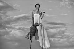 annonsering av wine Nätt flicka med vinflaskan över himmel Arkivbild
