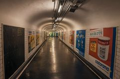 Annonsering i passagen som anknyter stationer av den Paris gångtunnelen Arkivbilder