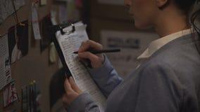 Annotazione dell'elaborazione del ricercatore criminale, annotante i dettagli di caso, indagine archivi video