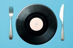 Annotazione di vinile con la forcella e coltello su un fondo blu Buon gusto nella musica fotografie stock libere da diritti