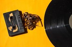 Annotazione di vinile e della cassetta su un fondo colorato arancio Fotografia Stock