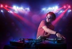 Annotazioni di miscelazione del DJ dell'adolescente davanti ad una folla in scena Fotografia Stock