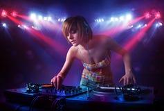 Annotazioni di miscelazione del DJ dell'adolescente davanti ad una folla in scena Immagini Stock
