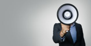 Announcement - businessman with megaphone in front of face Stock Photo