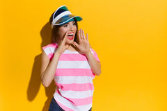 Announcement. Young woman in pink striped shirt and blue sun visor holding both hands on chin and shouting. Waist up studio shot on yellow background Stock Images