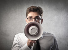Announcer. Young businessman talking into a megaphone Royalty Free Stock Photo