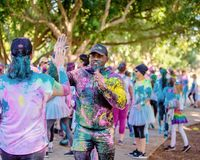 Announcer Encourages Woman In Color Frenzy Fun Run. MACKAY, QUEENSLAND, AUSTRALIA - JUNE 2019: Unidentified announcer with microphone and covered in colored dust stock images