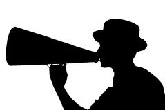 Announcer with Megaphone. A man in a vintage hat uses an old time megaphone to speak to a crowd Royalty Free Stock Image