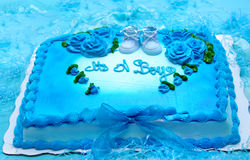 Announcing. Bright blue sheet cake is decorated with blue roses and scalloped edges.  Baby booties in blue announce it's a boy in piping.  Paper shreds and blue Stock Photos