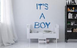Announcing the birth of a boy. With hand written letters above a simple white cot or crib in a neat kids nursery. 3d Rendering Stock Photos